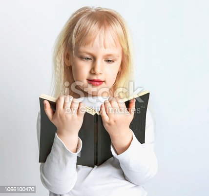 istock Portrait of cheerful smiling little schoolgirl girl with big book. 1066100470