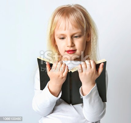 istock Portrait of cheerful smiling little schoolgirl girl with big book. 1066100492