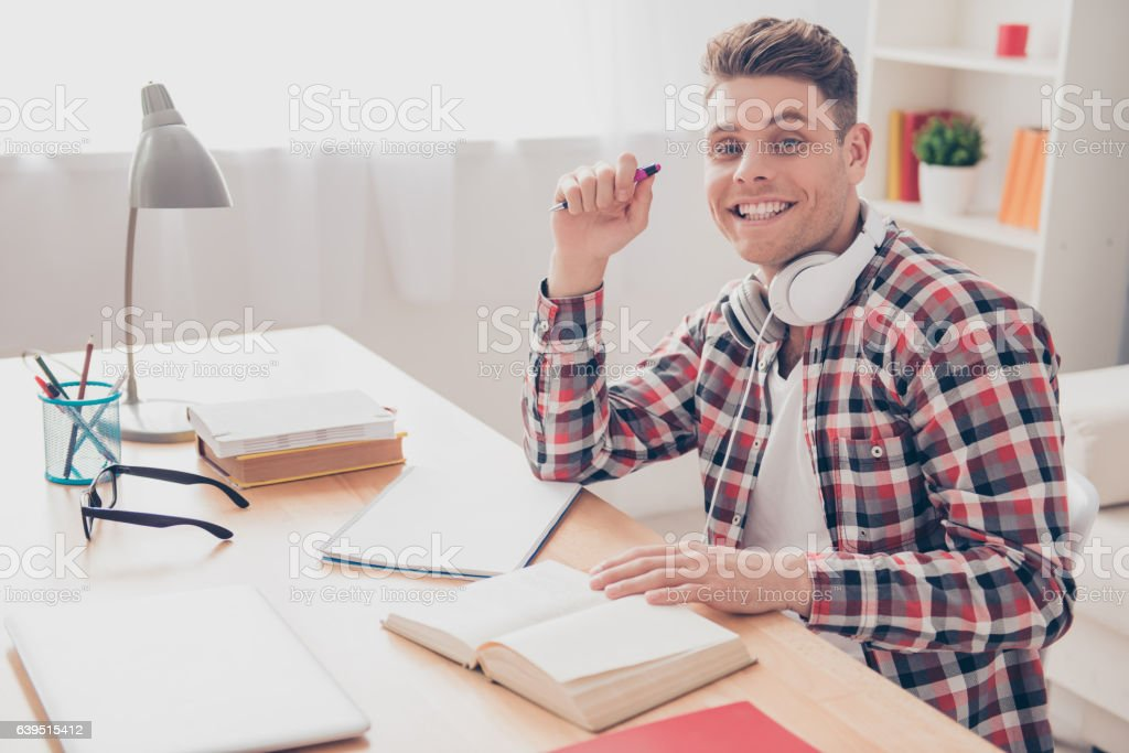 Portrait of cheerful smiling man with headphones reading book stock photo