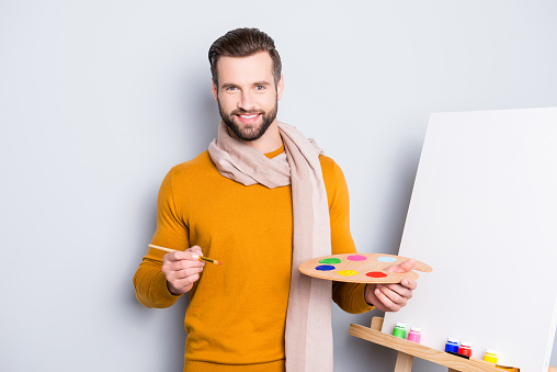 636761588 istock photo Portrait of cheerful stylish artist with scarf around neck, modern hairstyle, looking at camera holding colorful palette and brush in hands, isolated on grey background 970375416
