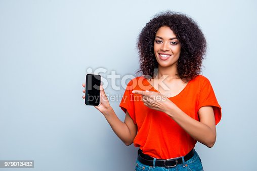 1132512759istockphoto Portrait of cheerful stylish girl showing black touch screen of smart phone pointing with forefinger at copyspace empty place looking at camera isolated on grey background 979013432