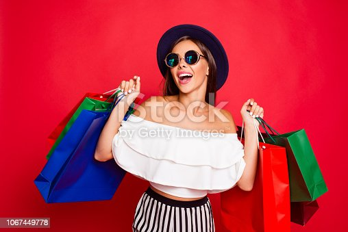 istock Portrait of cheerful stylish trendy attractive straight-haired lady wearing eyeglasses eyewear white off-the-shoulders ruffles blouse top enjoying leisure colorful bags isolated over red background 1067449778