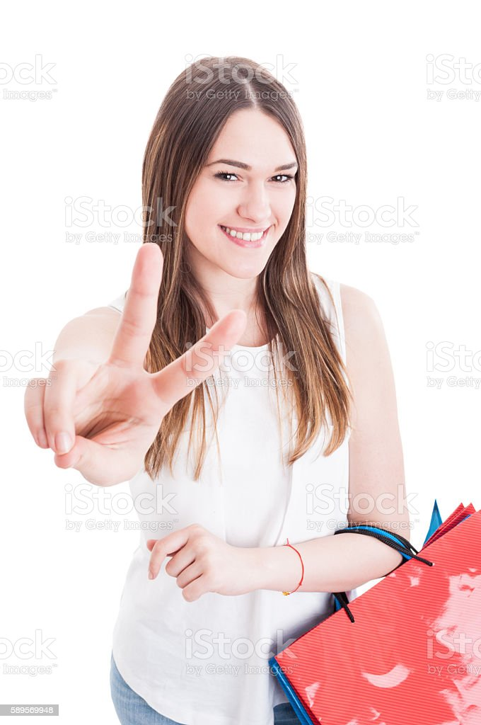 Portrait of cheerful successful girl doing victory sign and smil stock photo