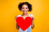 istock Portrait of cheerful toothy girl with beaming smile having big carton paper heart in hands looking at camera isolated on yellow background. Rest relax leisure concept 979977604