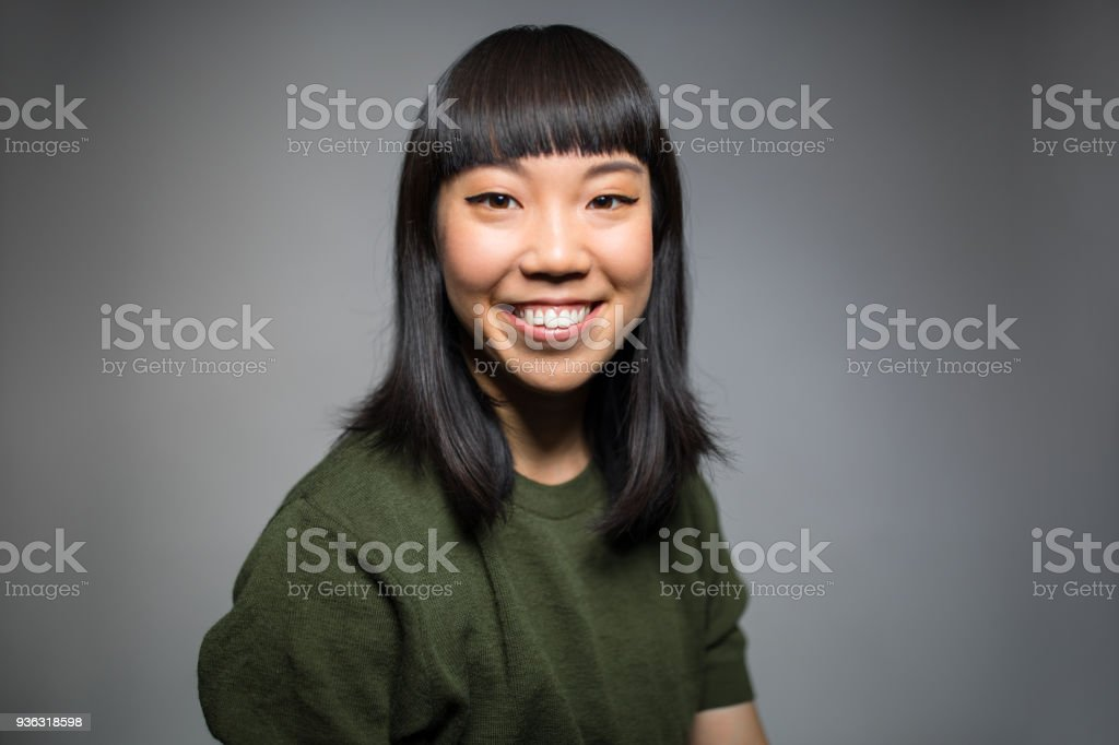 Portrait of cheerful woman against gray background stock photo