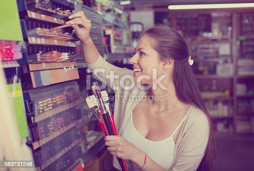 594918592 istock photo Portrait of cheerful woman choosing brushes for drawing 583731248