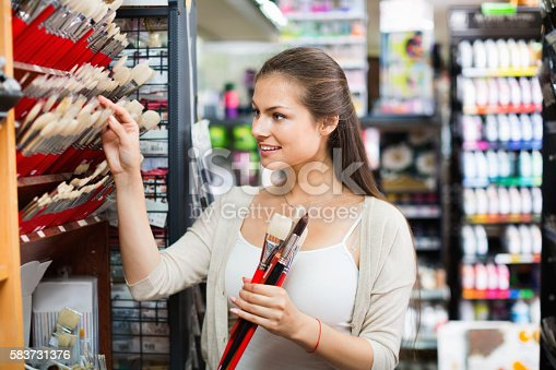 594918592 istock photo Portrait of cheerful woman choosing brushes for drawing 583731376