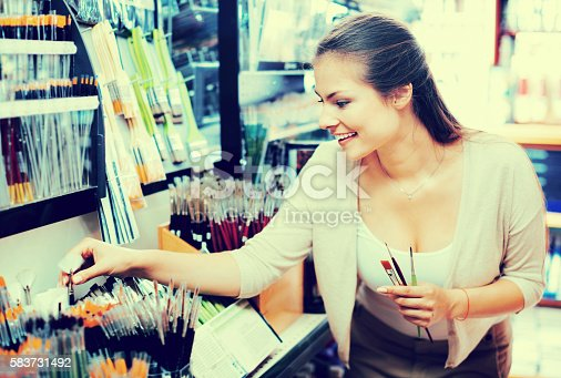 594918592 istock photo Portrait of cheerful woman choosing brushes for drawing 583731492