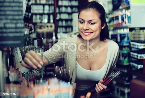 594918592 istock photo Portrait of cheerful woman choosing brushes for drawing 583732876