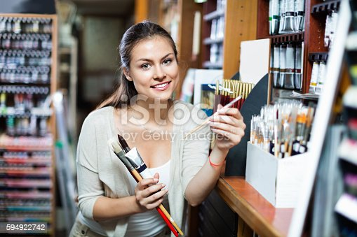 594918592 istock photo Portrait of cheerful woman choosing brushes for drawing 594922742