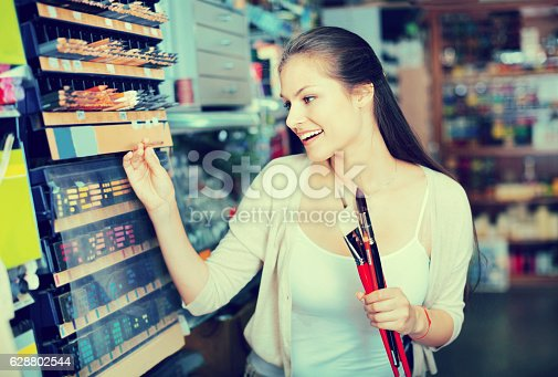 594918592 istock photo Portrait of cheerful woman choosing brushes for drawing 628802544