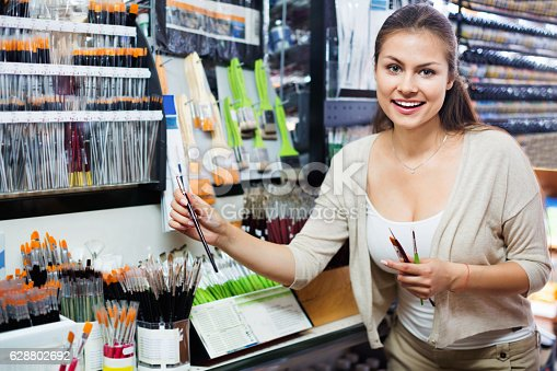 594918592 istock photo Portrait of cheerful woman choosing brushes for drawing 628802692
