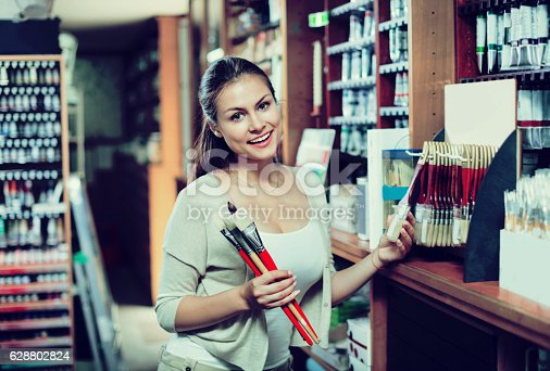 594918592 istock photo Portrait of cheerful woman choosing brushes for drawing 628802824