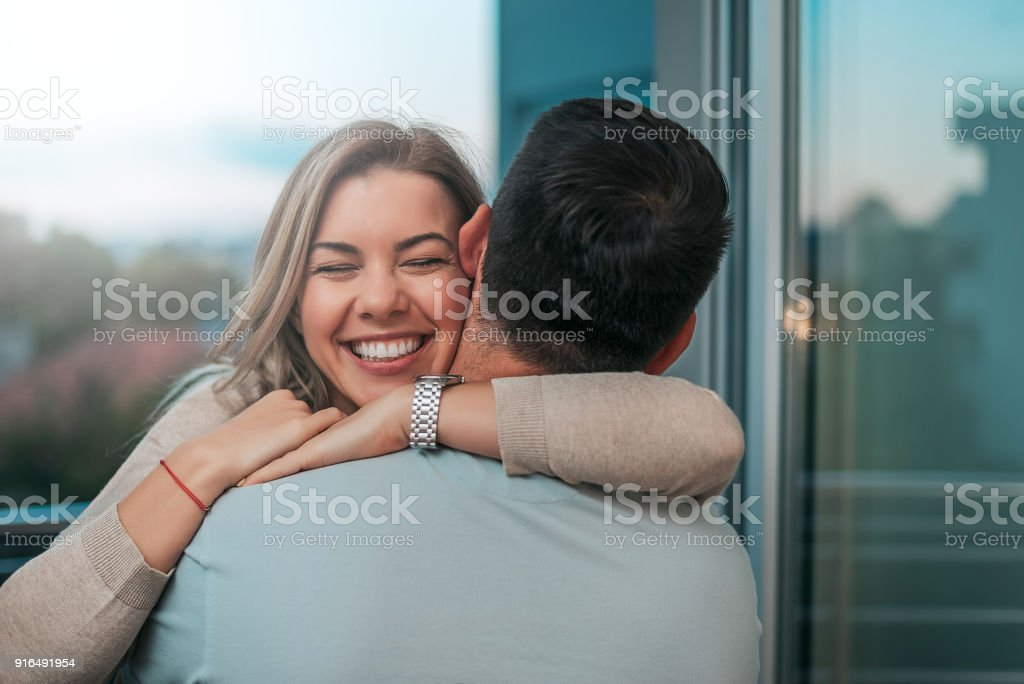 Portrait of cheerful woman hugging man. stock photo