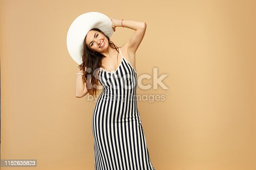 Portrait of cheerful woman in black and white striped dress, hat standing, looking camera isolated on pastel beige background in studio. People sincere emotions, lifestyle concept. Mock up copy space