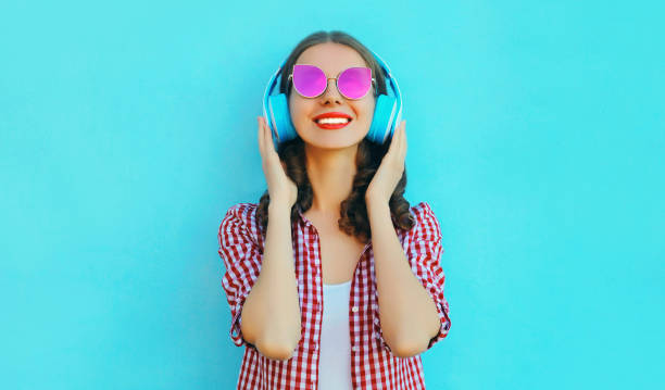 Portrait of cheerful woman in wireless headphones listening to music wearing a pink sunglasses on colorful blue background stock photo