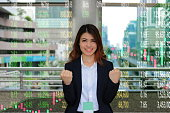 Portrait of cheerful young Asian business woman raising hands and looking at camera with candlestick chart patterns uptrend background. Investment growth concept