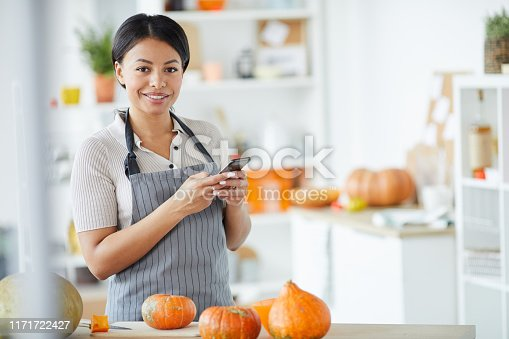 Portrait of cheerful young Black woman in stripped apron texting sms on smarphone while preparing for Halloween