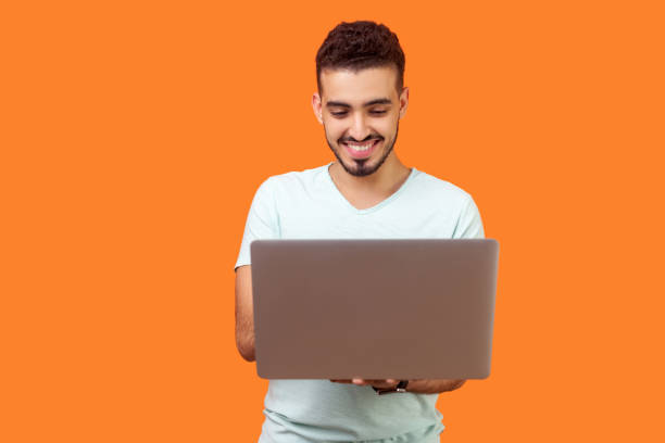 Portrait of cheerful young brunette man typing on laptop, surfing the web. indoor studio shot isolated on orange background stock photo