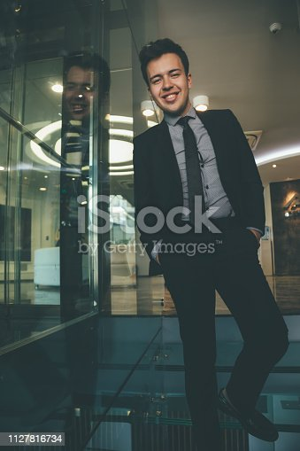 825082848istockphoto Portrait of cheerful young businessman in office 1127816734