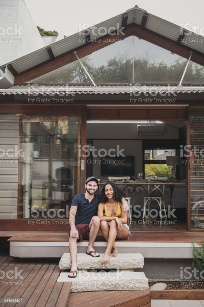 Portrait of cheerful young couple sitting on step outside house smiling stock photo