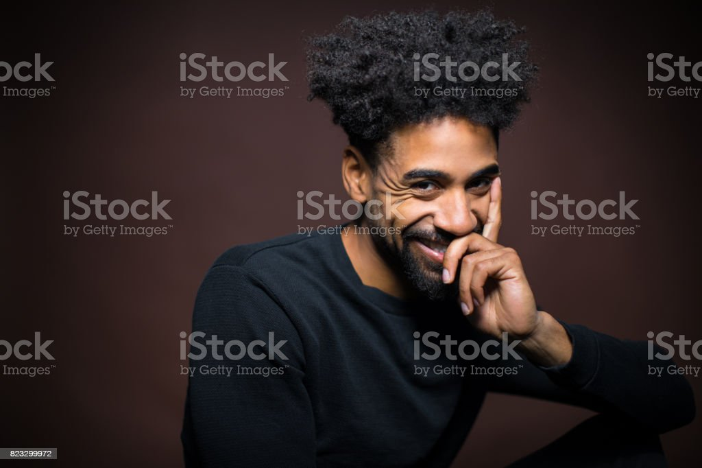 Portrait Of Cheerful Young Man With Hand On Chin stock photo