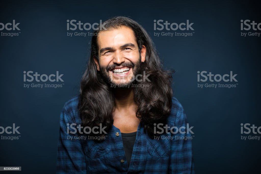 Portrait Of Cheerful Young Man With Long Hair stock photo