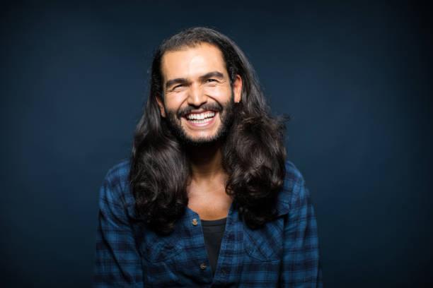 porträt von fröhlichen jungen mann mit langen haaren - alvarez stock-fotos und bilder