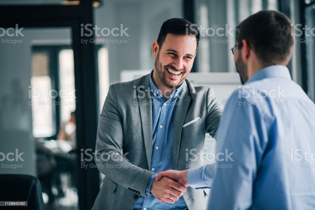 Portrait of cheerful young manager handshake with new employee. royalty-free stock photo