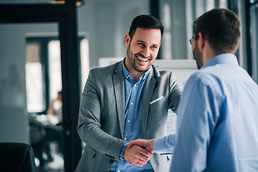 Portrait Of Cheerful Young Manager Handshake With New