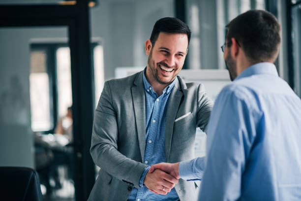 portrait of cheerful young manager handshake with new employee. - handshake stock pictures, royalty-free photos & images