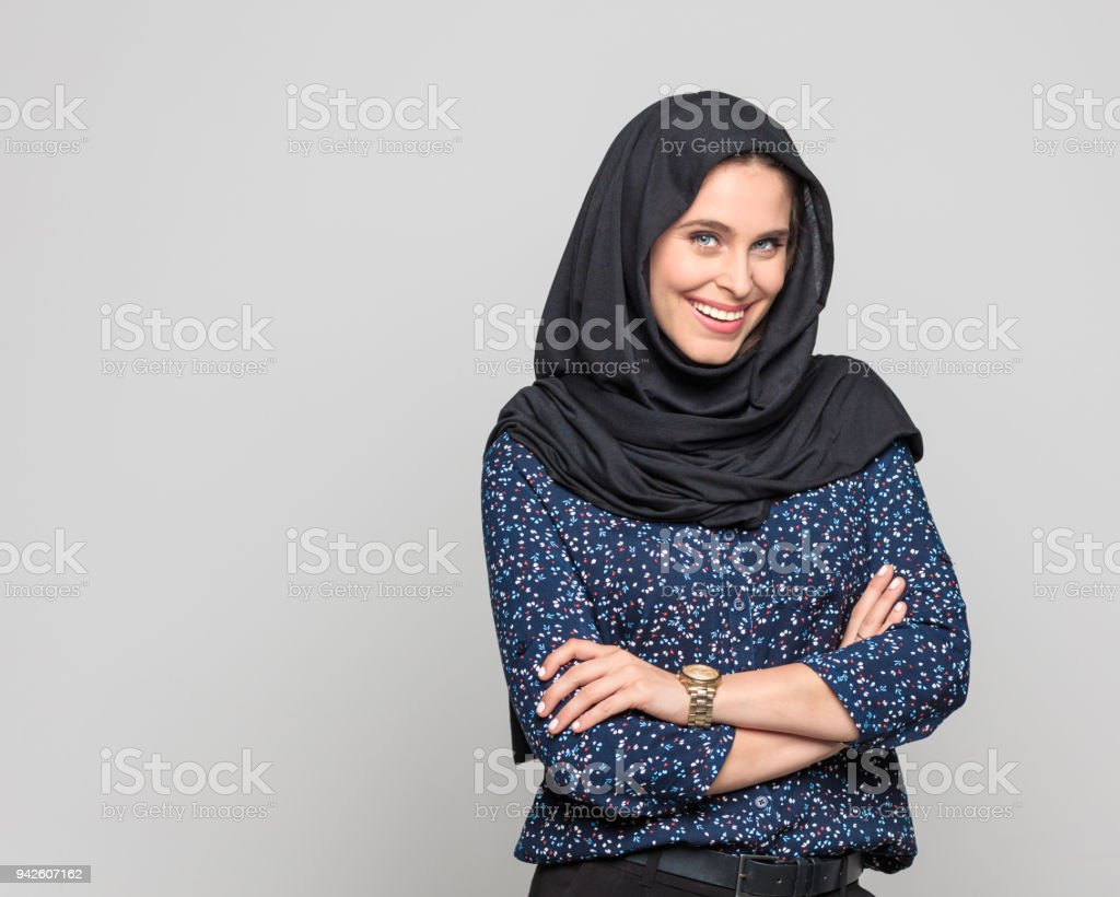 Portrait of cheerful young muslim woman Portrait of cheerful young muslim woman. Businesswoman in hijab looking at camera against grey background. 20-29 Years Stock Photo
