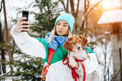 istock Portrait of cheerful young woman in warm stylish clothes and bagpack take selfie on smartphone with her beagle dog in winter park. Friendship, pet and human. 1129793584