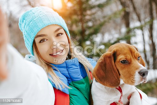 istock Portrait of cheerful young woman in warm stylish clothes and bagpack take selfie on smartphone with her beagle dog in winter park. Friendship, pet and human. 1129793587