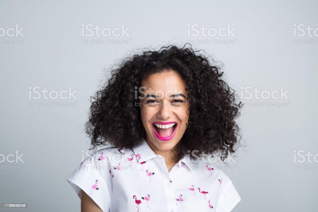 Portrait of cheerful young woman Portrait of cheerful young woman laughing on gray background 20-24 Years Stock Photo