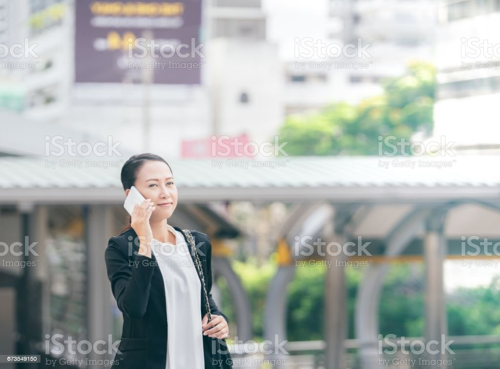 Portrait of cheerful young woman talking on smartphone and laughing outdoors. Happy beautiful caucasian business woman using mobile phone, making call on the street in city. Copy space royalty-free stock photo