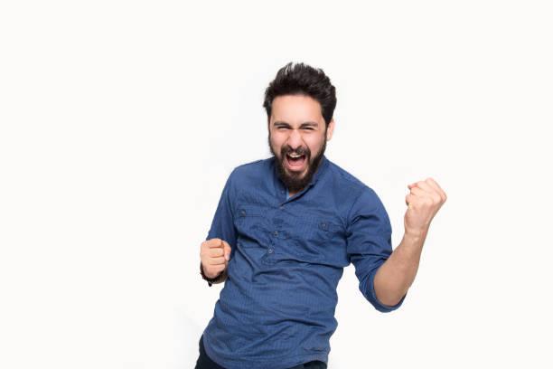 portrait of cheering young man screaming in happiness against white background - buona notizia foto e immagini stock
