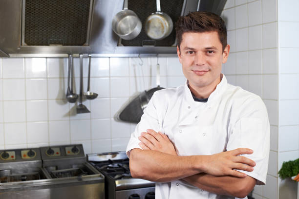 Portrait Of Chef Wearing Whites Standing By Cooker In Kitchen Portrait Of Chef Wearing Whites Standing By Cooker In Kitchen chef's whites stock pictures, royalty-free photos & images