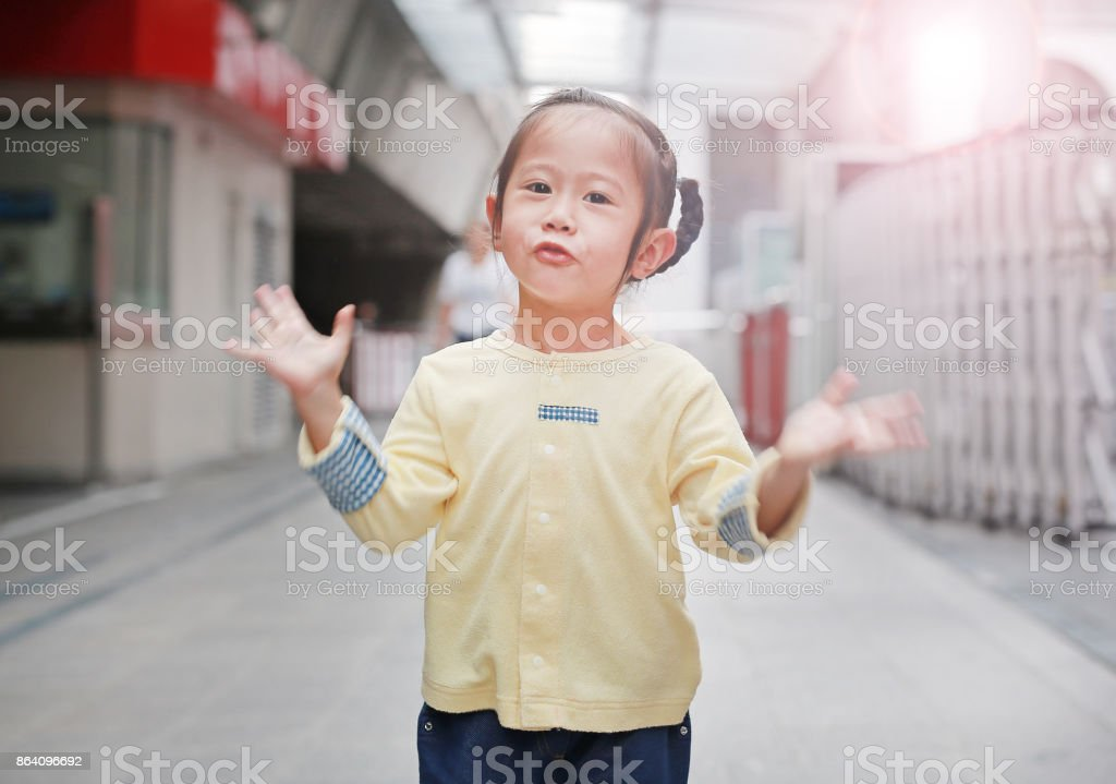 Portrait of child girl open arm standing in sky train station at morning. royalty-free stock photo