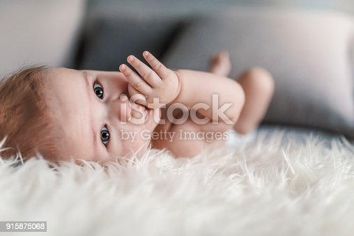 Close up portrait of infant sucking thumb and lying on white fluffy  bed indoors. Photo of the boy at the age of four months. He is holding his thumb in mouth. Baby boy sucking his fingers instead of mother breastfeeding