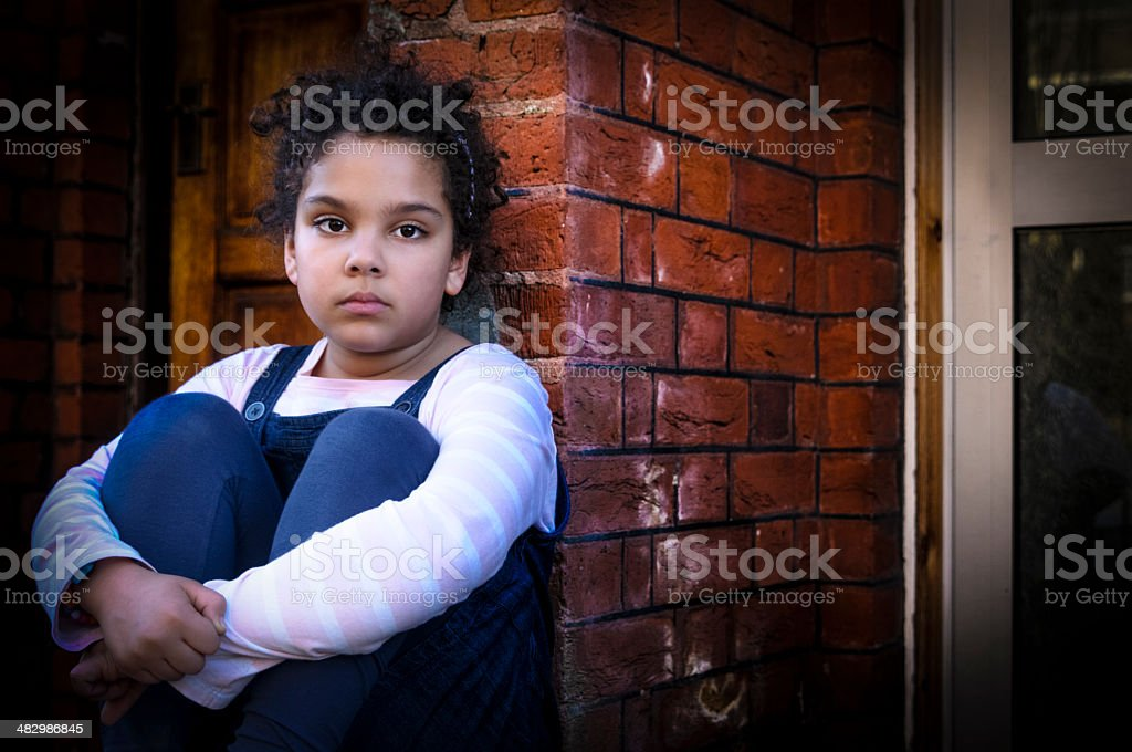 PEOPLE: Portrait Of Child (7-8) Sitting Outside stock photo