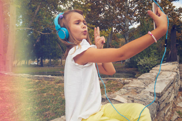Portrait of child using cellphone and listening music outdoors. stock photo