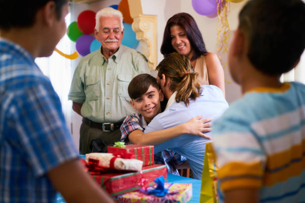 portrait of child with family and friends celebrating birthday - jugendliche geburtstag geschenke stock-fotos und bilder