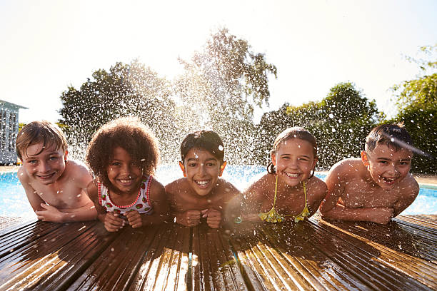 Portrait Of Children Having Fun In Outdoor Swimming Pool - foto de stock