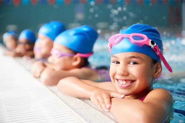 retrato de niños en el agua en el borde de la piscina esperando la lección de natación - natación fotografías e imágenes de stock