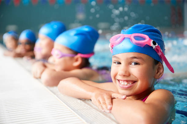 Portrait Of Children In Water At Edge Of Pool Waiting For Swimming Lesson Portrait Of Children In Water At Edge Of Pool Waiting For Swimming Lesson swimming goggles stock pictures, royalty-free photos & images