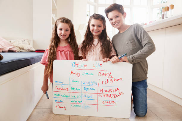 Portrait Of Children Making List Of Chores On Whiteboard At Home Portrait Of Children Making List Of Chores On Whiteboard At Home allowance stock pictures, royalty-free photos & images