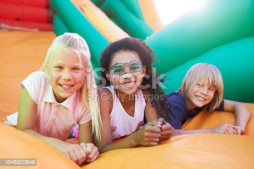 Portrait Of Children On Inflatable Slide At Summer Garden Fete