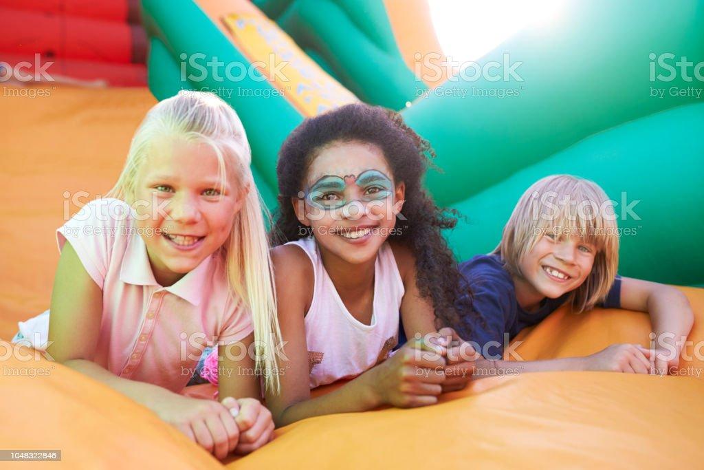 Portrait Of Children On Inflatable Slide At Summer Garden Fete stock photo