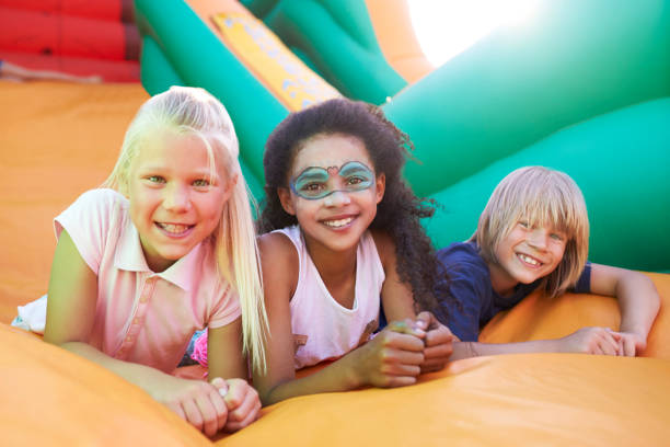 Portrait Of Children On Inflatable Slide At Summer Garden Fete stock photo